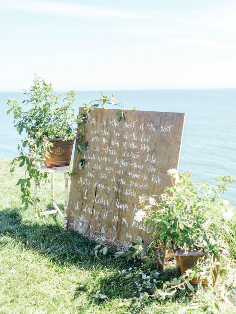 Hand lettered love signage and foliage on the wedding bluff at Villa Della Famiglia for a Summer wedding.