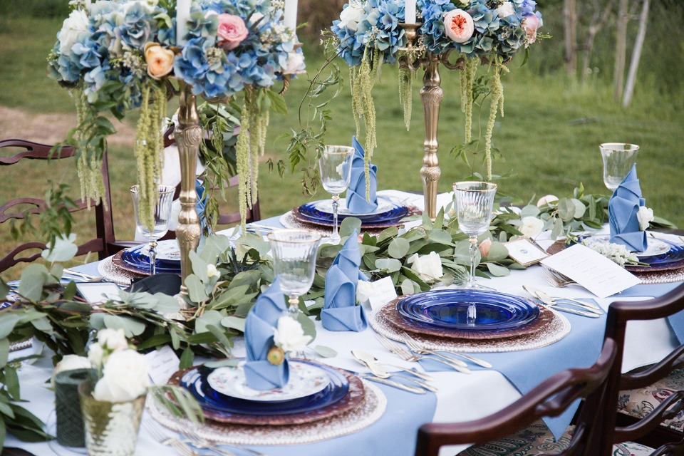 Blue and white table decor with greenery garland