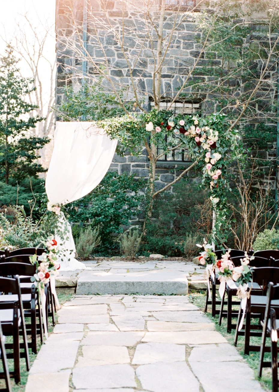 outdoor wedding ceremony with dramatic floral backdrop