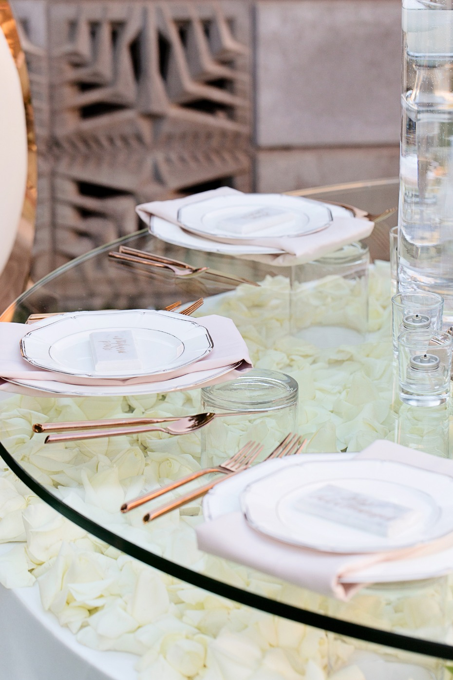 glass topped wedding table with flower petals underneith