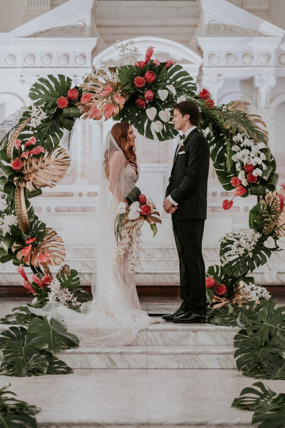 Love this tropical glam ceremony arch with gold and green palm leaves