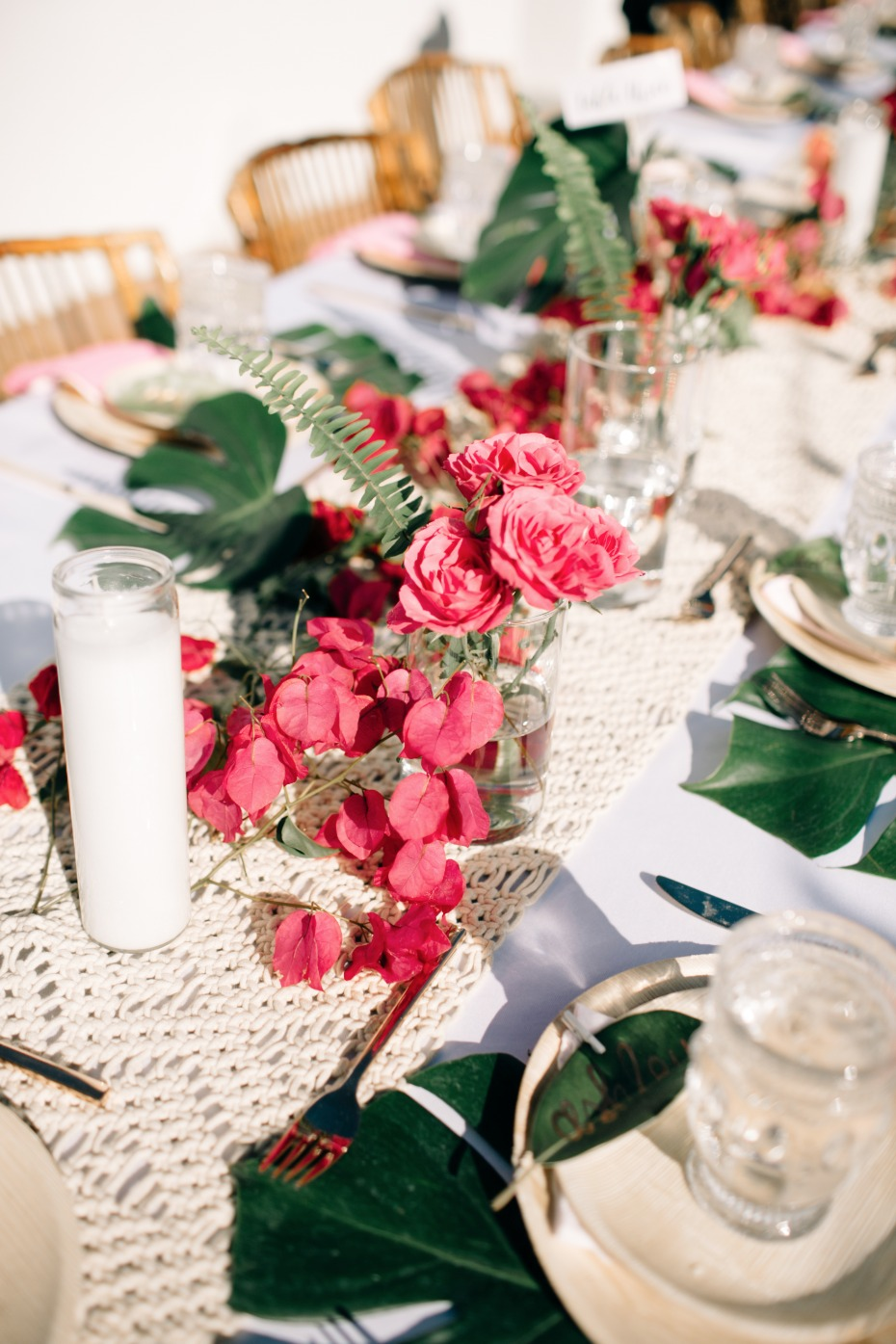 simple table arrangements of red roses, bougainvillea and ferns placed in small vases