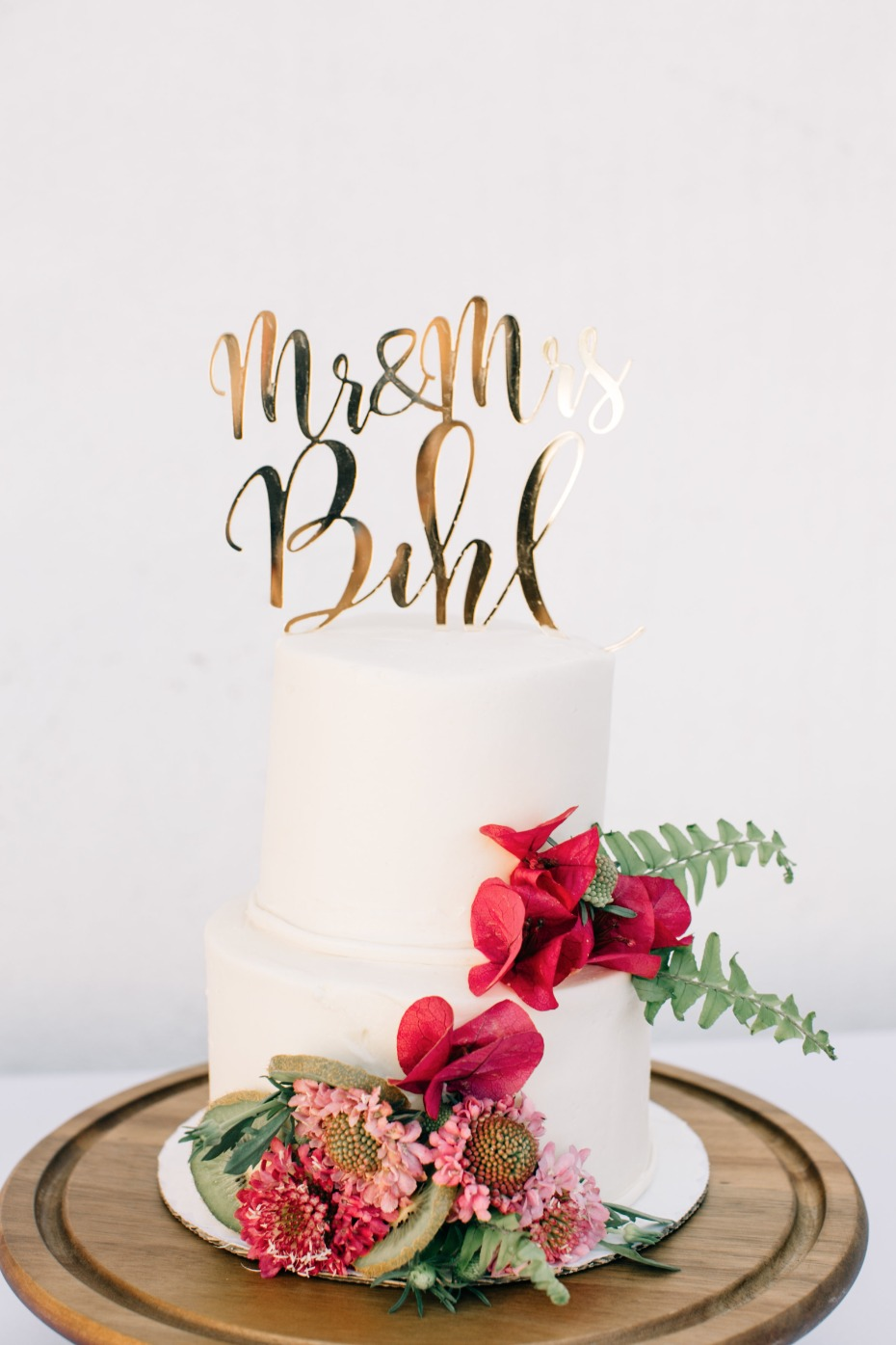 white wedding cake with gold cake toppber