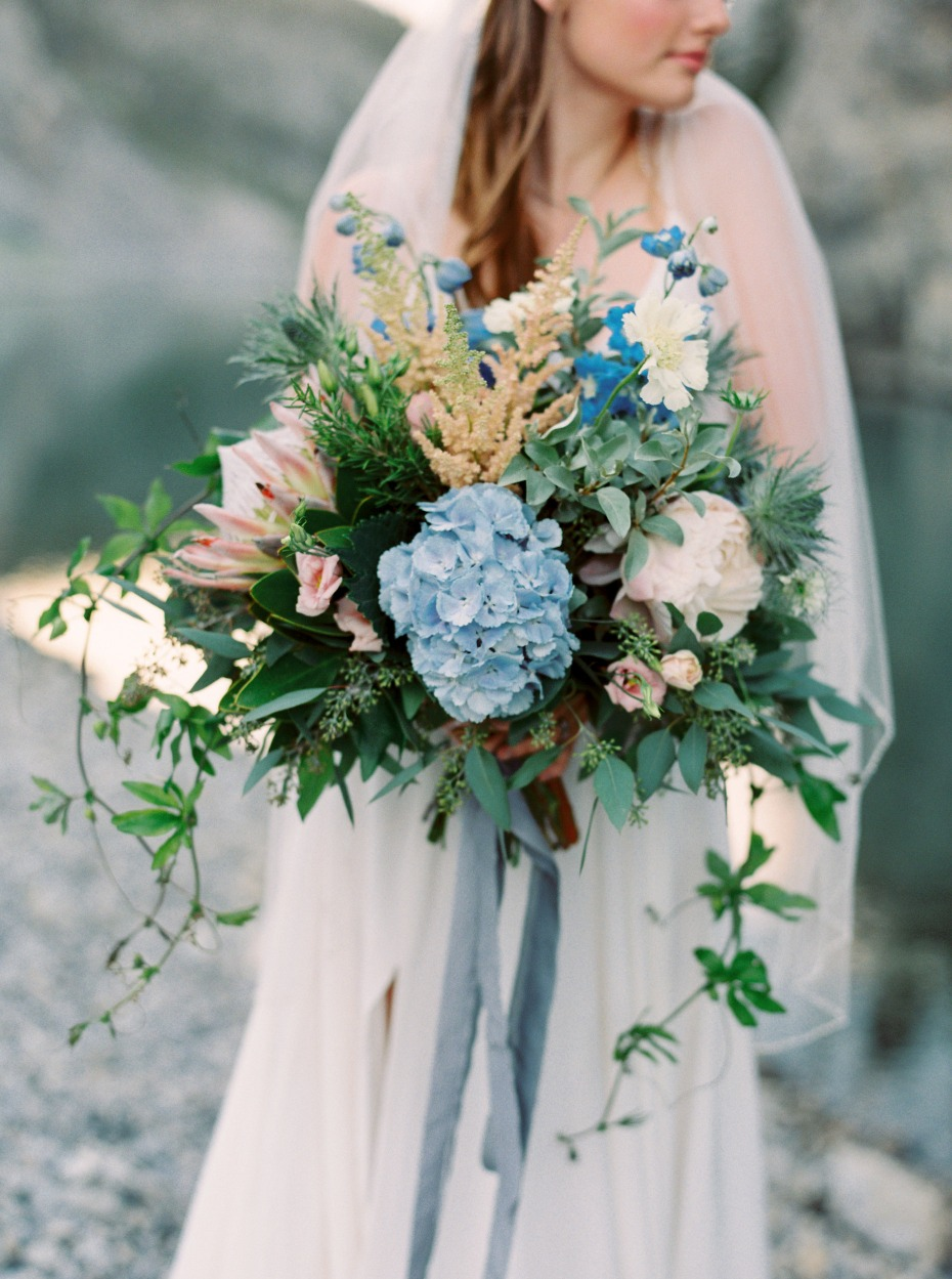 bride with her blue and pink wedding bouquet