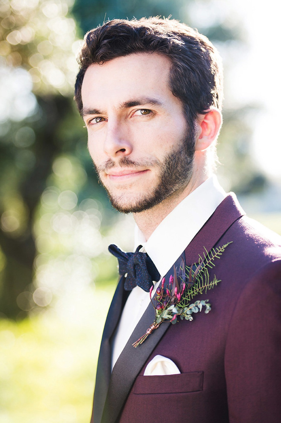 groom in burgundy suit jacket