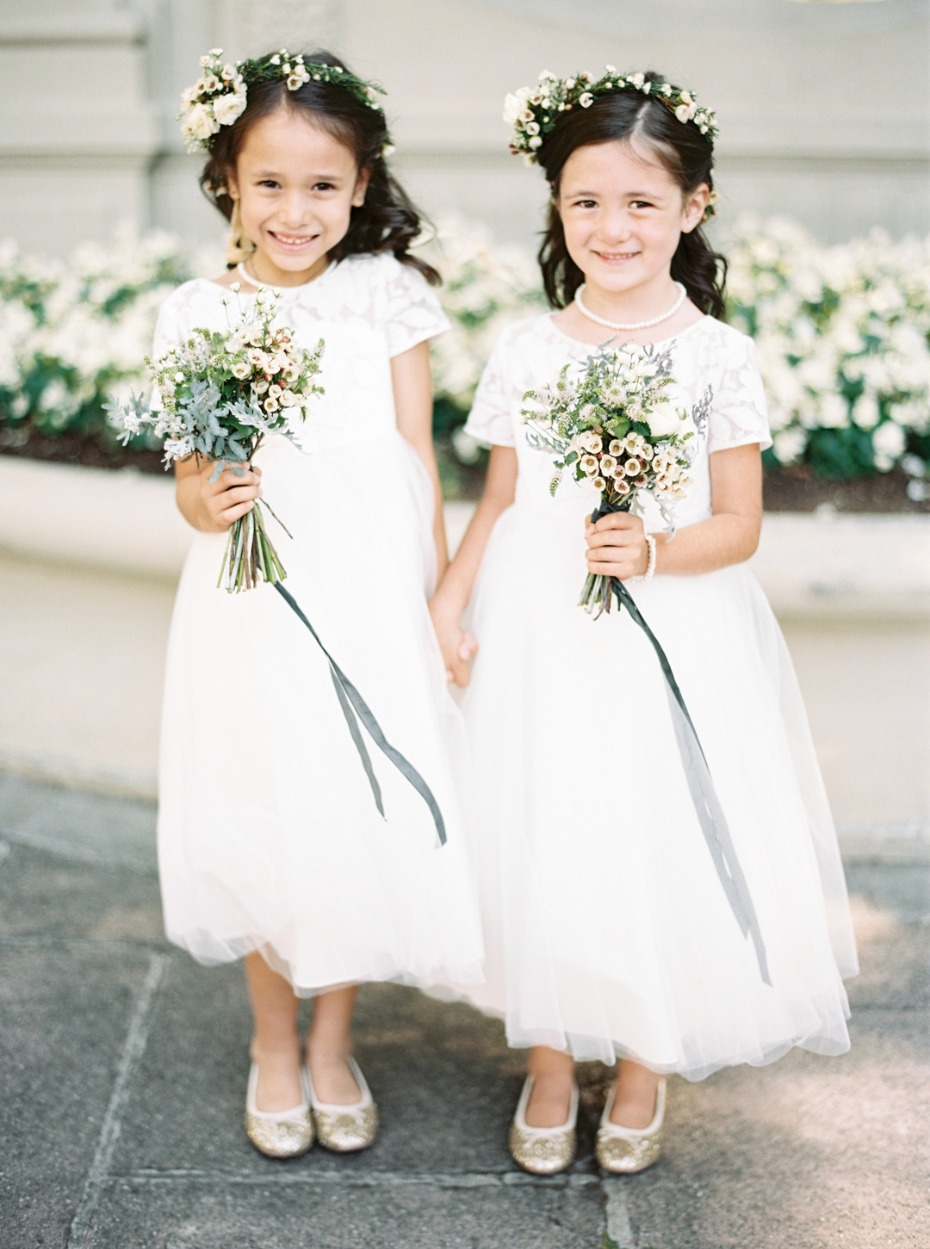 Flower girls with bouquets and ribbons