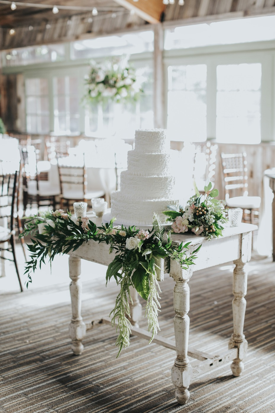 white wedding cake with cascading floral decor