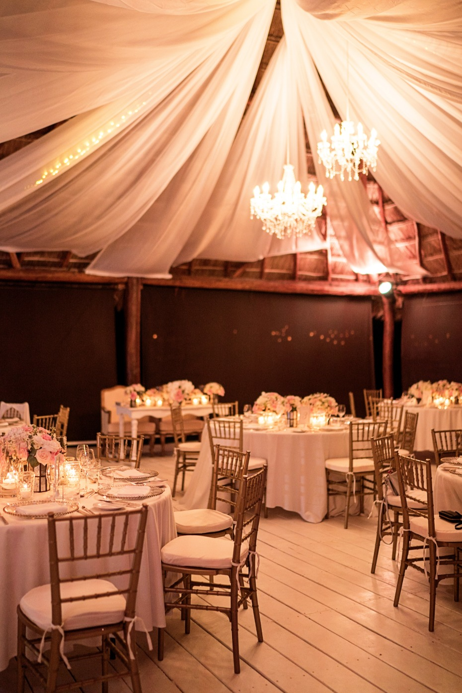 Dreamy candle lit reception with chandeliers