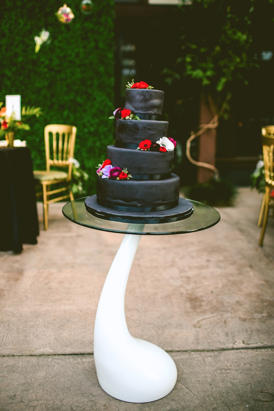 Black wedding cake with jewel toned blooms