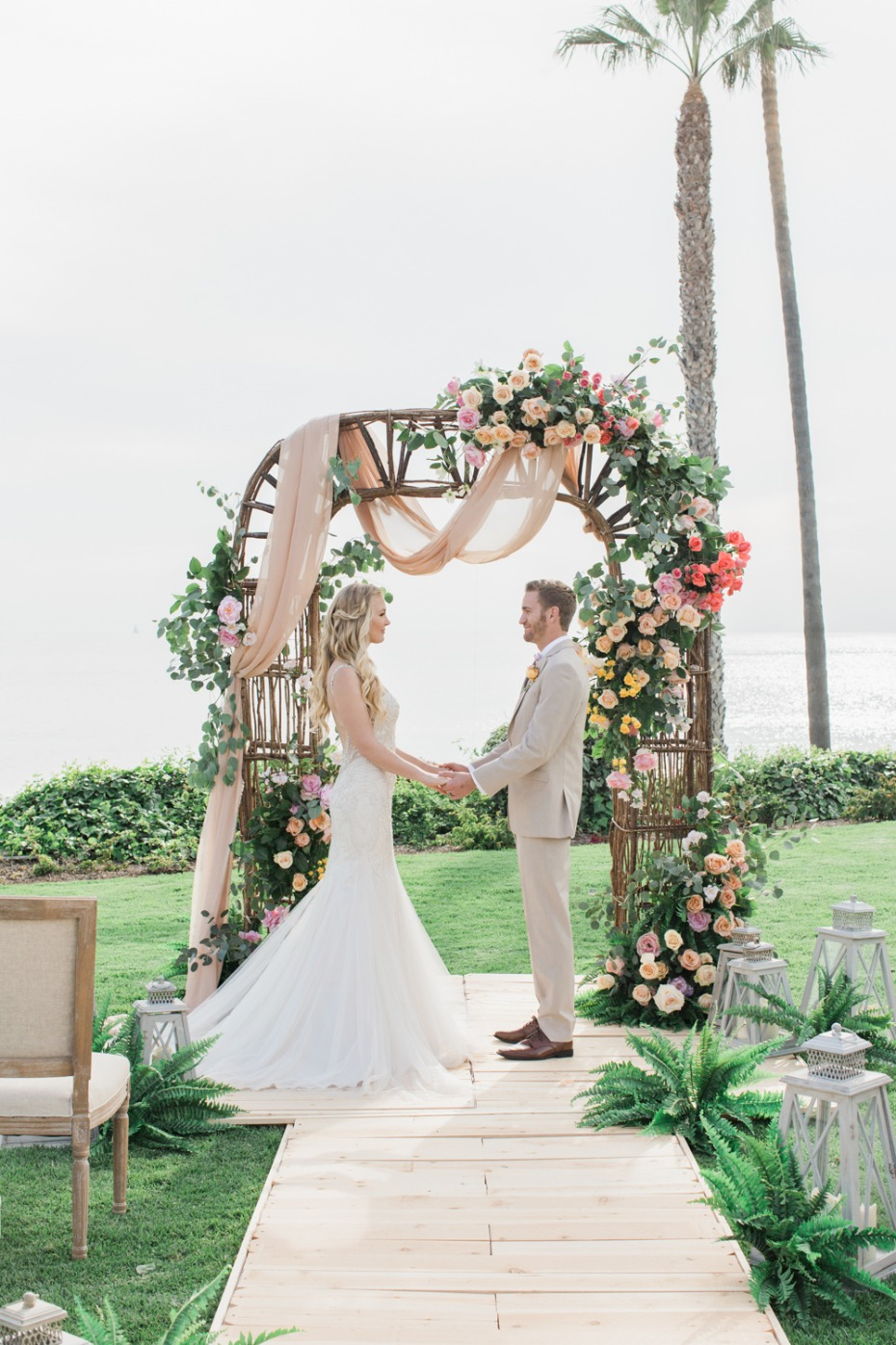 Colorful oceanfront wedding with rose arbor