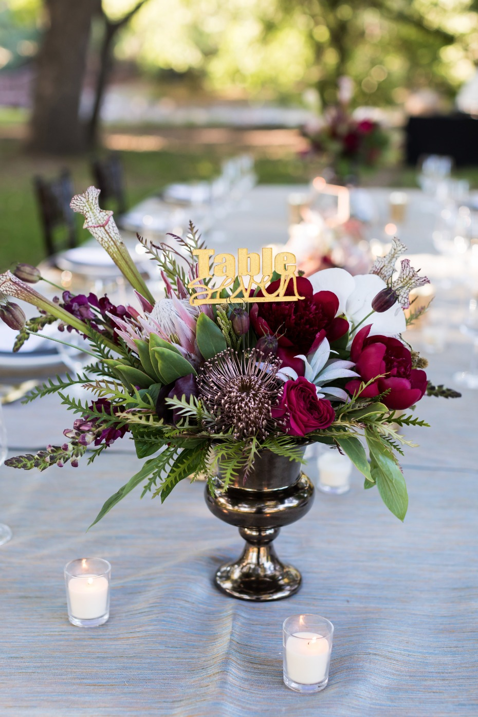 gold table numbers and floral centerpiece