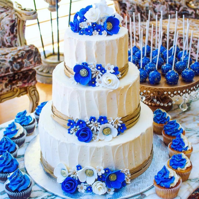 Something blue for your wedding ~ Royal Blue Anemome Flowers on tiered wedding cake, cupcakes & cake pops! Gold Chandelier Cake Stand