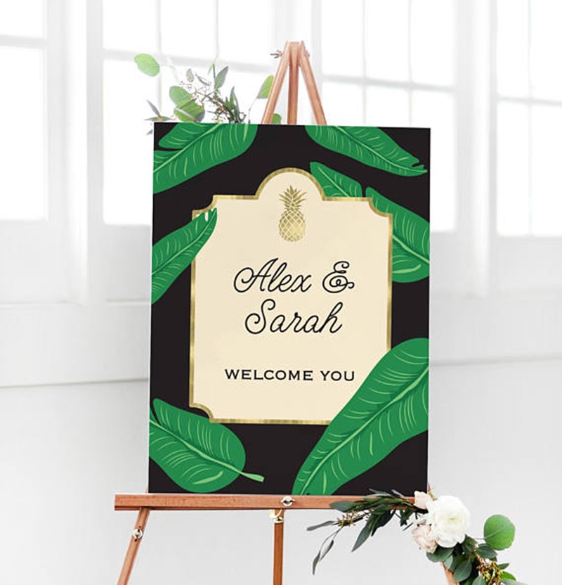 Miss Design Berry's awesome black and gold wedding welcome sign features hand illustrated palm frond and a gold pineapple for a cool