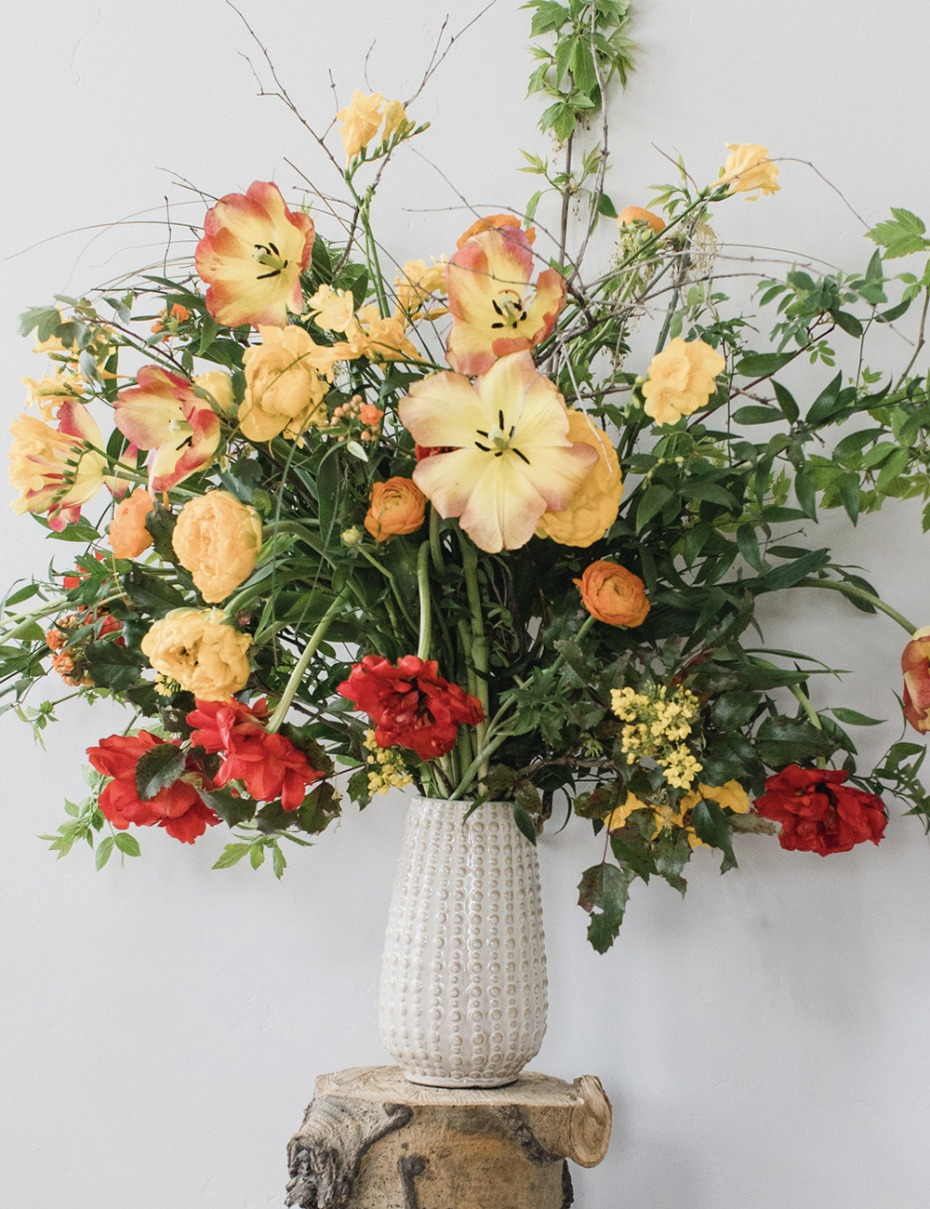 organic yellow and red flower arrangement mixed in with greenery