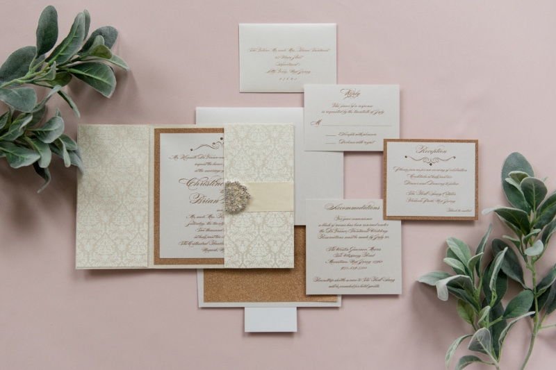 Square gatefold custom wedding invitation created with handmade damask-patterned paper, a double scroll clasp and rose gold glitter