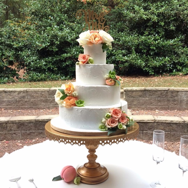 Tiered white wedding cake and fresh flowers look gorgeous on gold cake stand created by Opulent Treasures