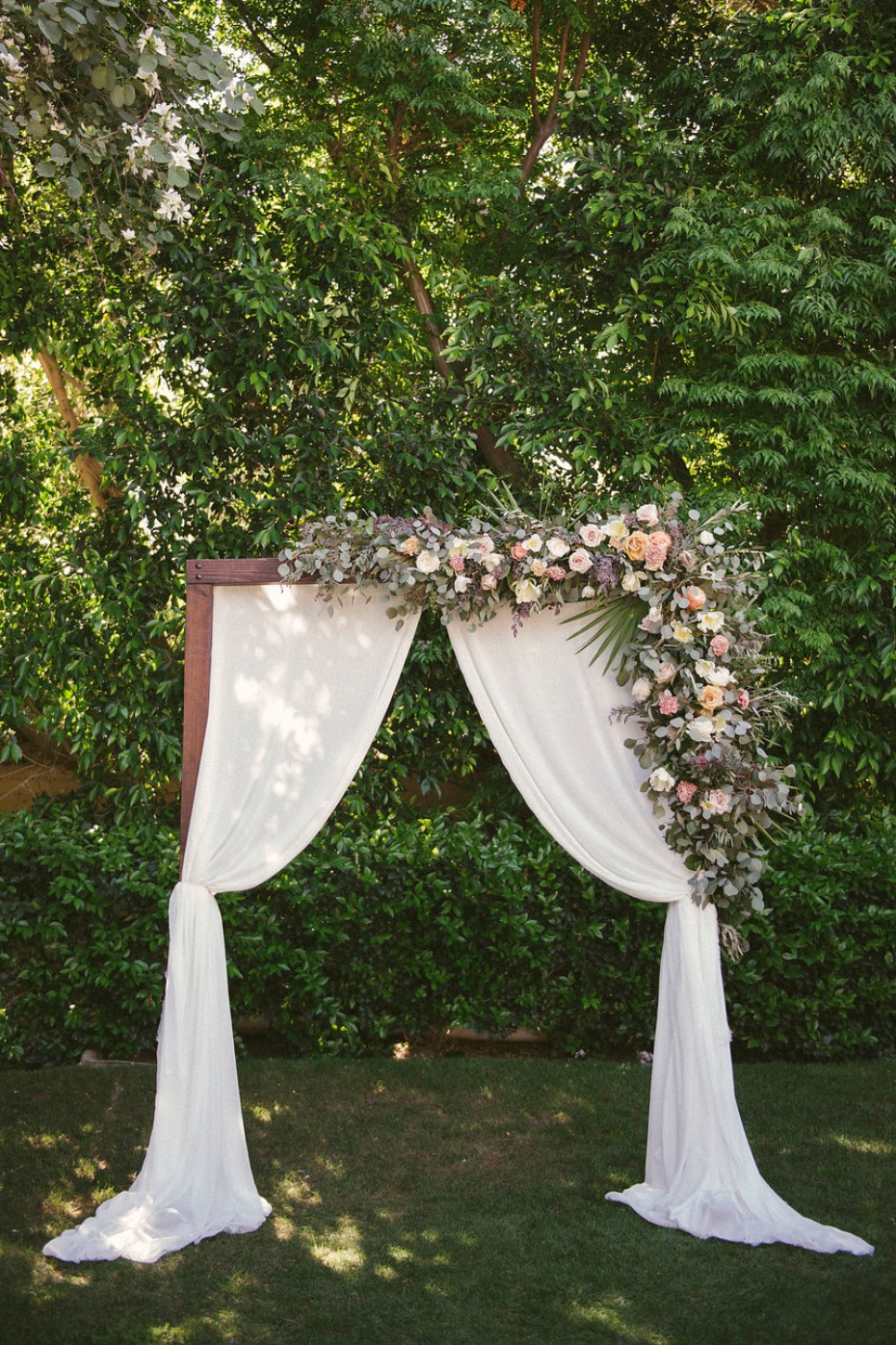Picture perfect arch with draped fabric and garden florals