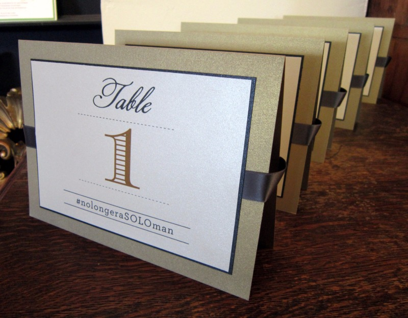 Some pretty gold and black table numbers, all in a row, including your hashtag! Designed by Persnickety Invitation Studio.