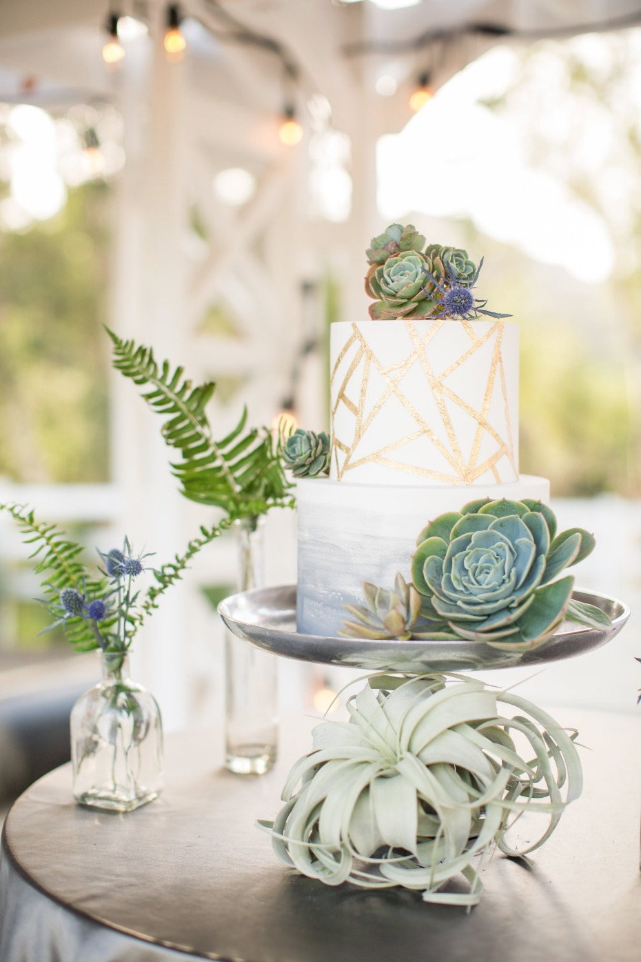gold geometric wedding cake topped with succulents