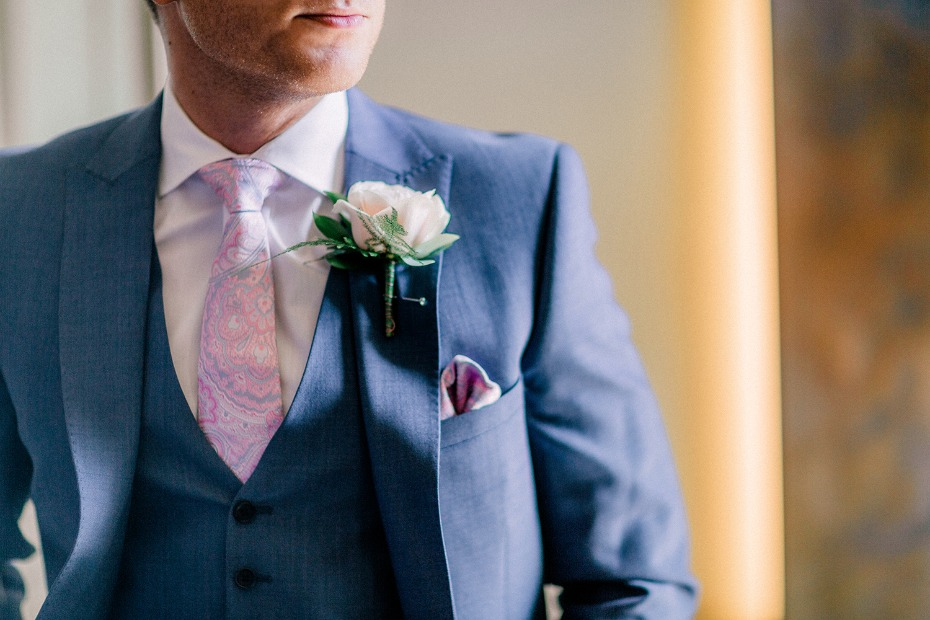 groom in blue suit with pink rose boutonniere