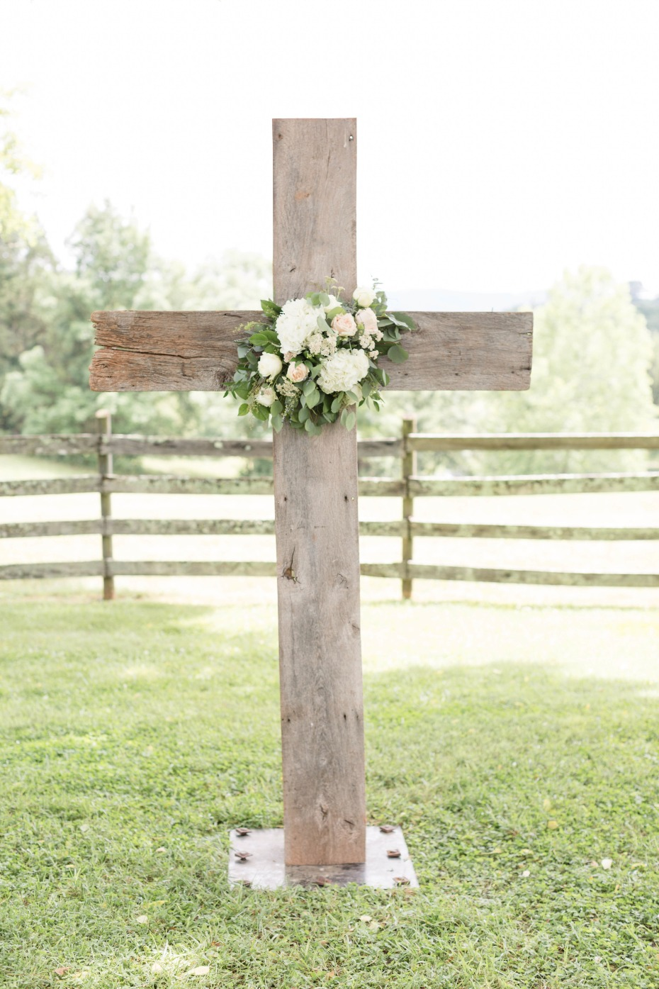 wooden cross decorated with flowers for wedding ceremony
