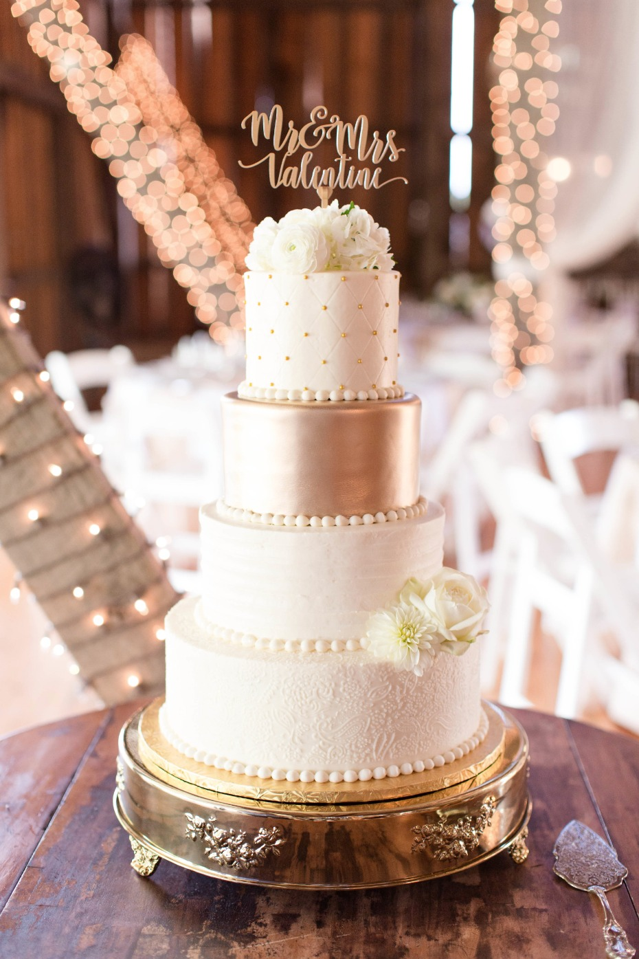 gold and white wedding cake on gold cake stand