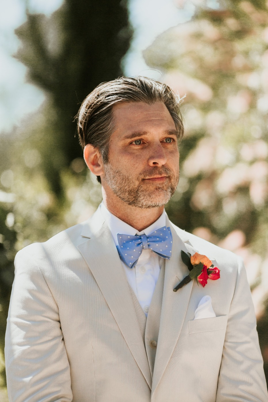 groom in tan suit and blue bow tie