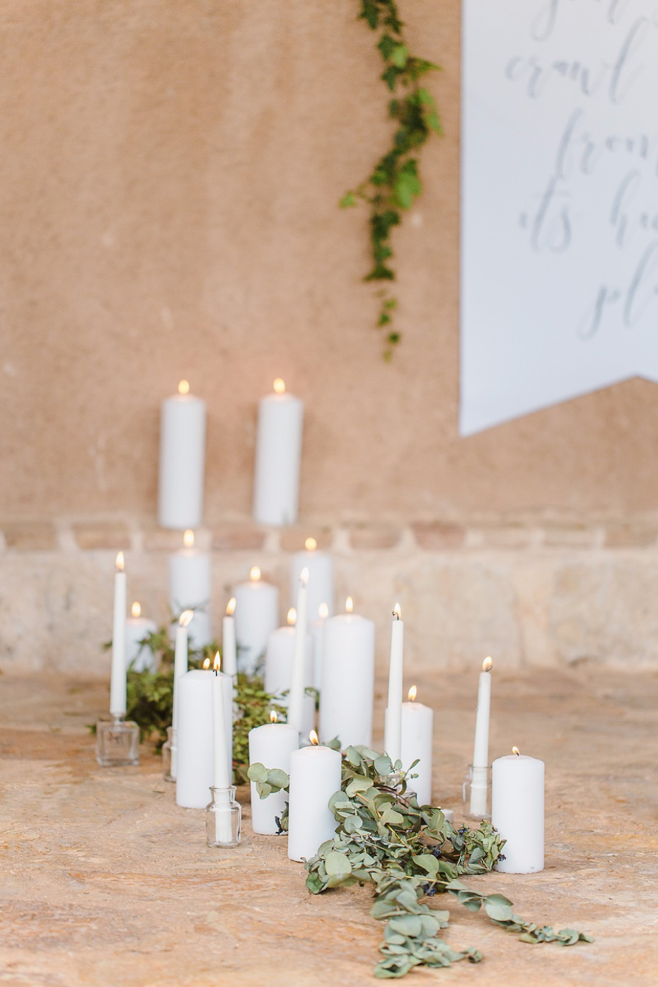 White candles and eucalyptus ceremony decor