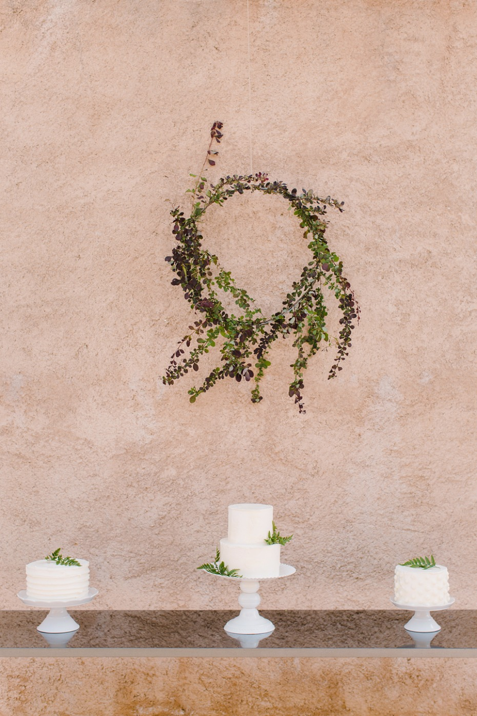 Minimalist cake table with white cakes and greenery