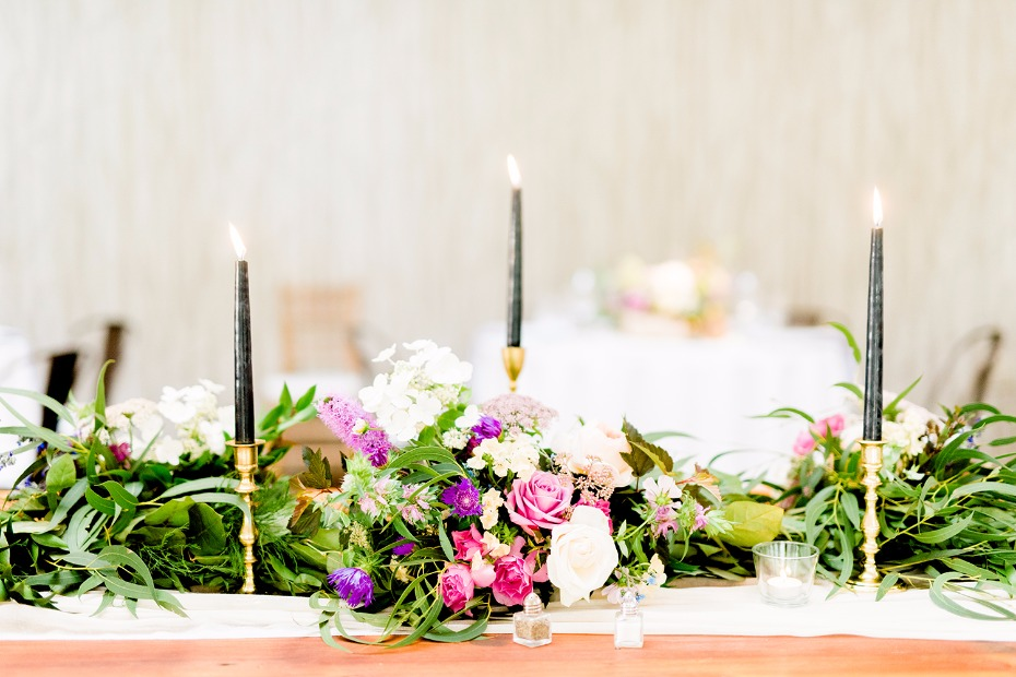 Black candle sticks and purple + green centerpiece