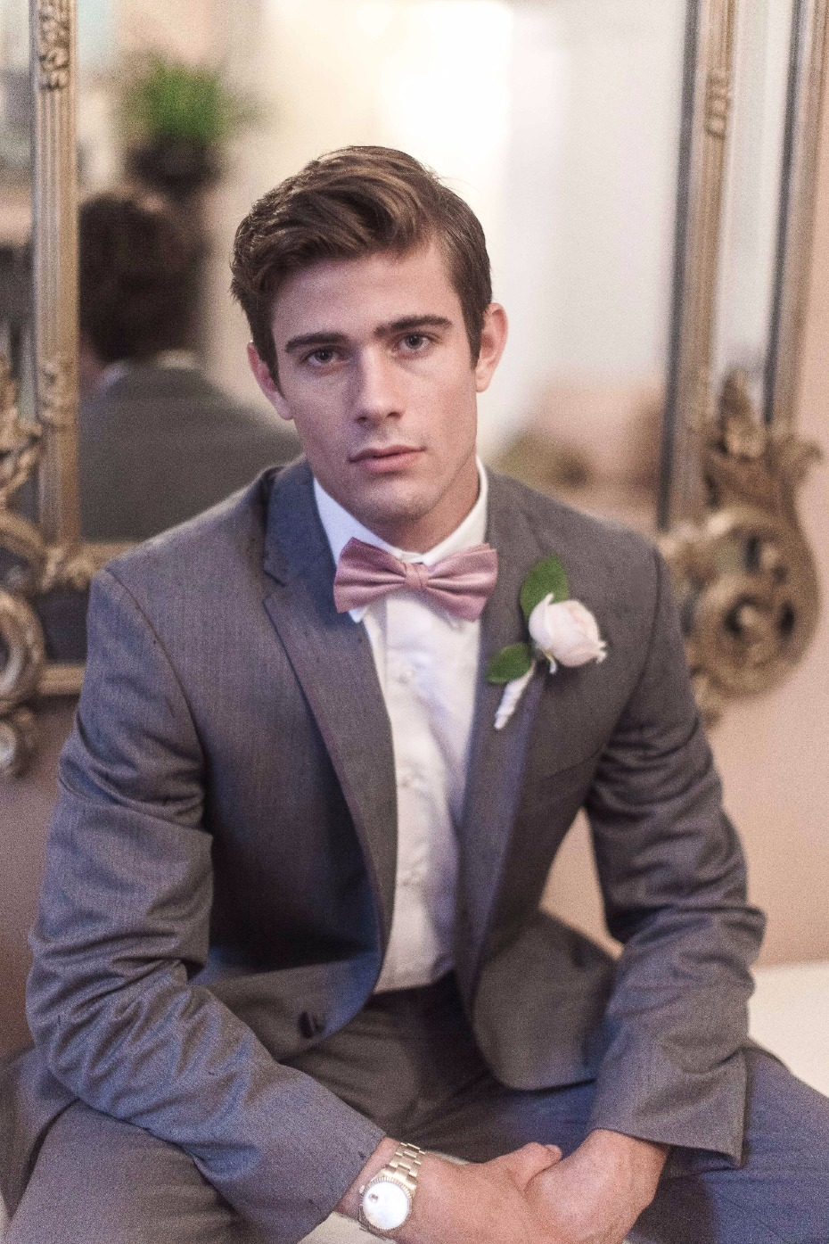 groom in pink bow tie and grey suit