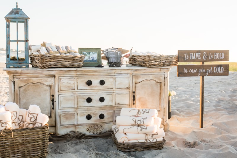 A blanket and pashmina welcome station is the perfect touch for a Fall beach wedding. Photography: Laura Napoli Photography | Coordinating