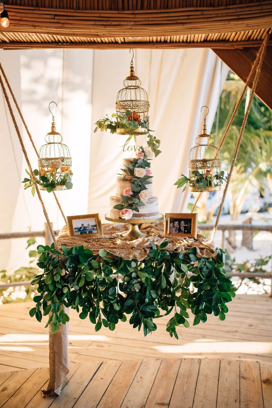 hanging wedding cake table with vintage birdcages and cascading vines
