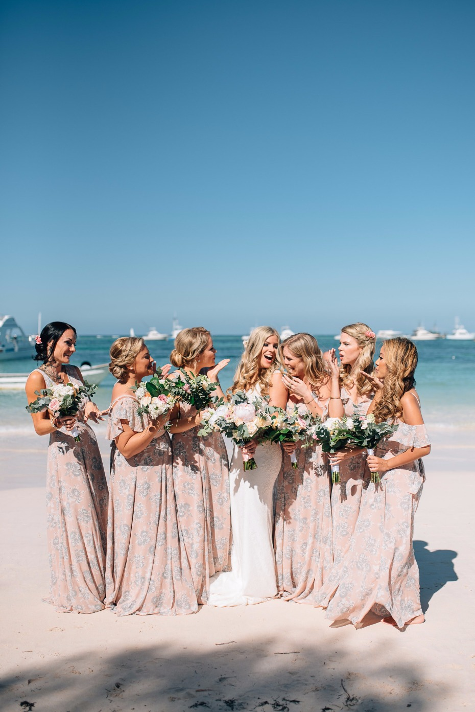 bridesmaids in long pink floral dresses on the beach in Mexico