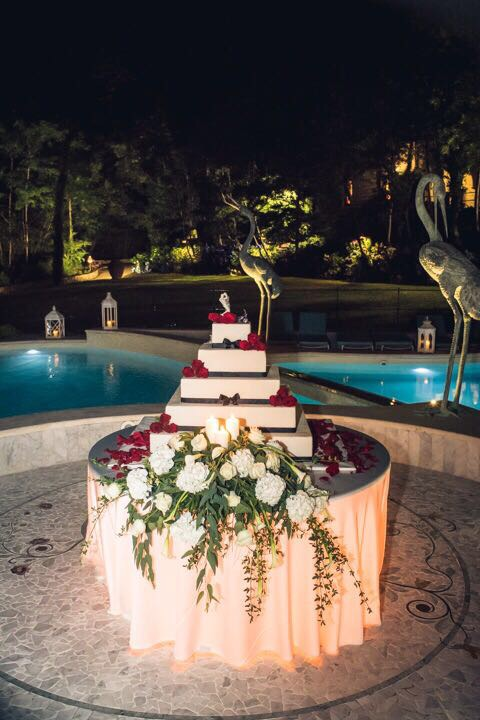 A minimal chic #weddingcake. Perfect geometry, a striking sheath of white flowers and a simple scattering of red petals at Valle Di