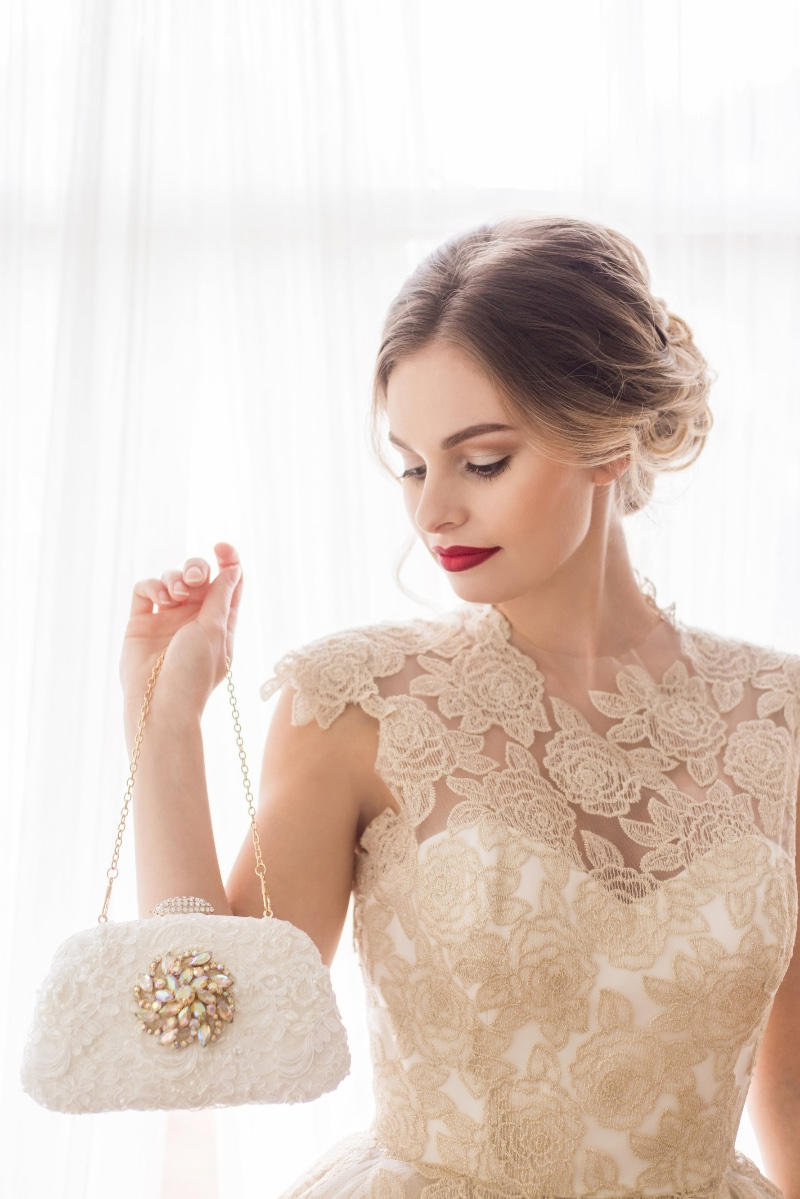 Carry your wedding essentials in a gorgeous Ivory and lace bridal clutch with a touch of sparkle.