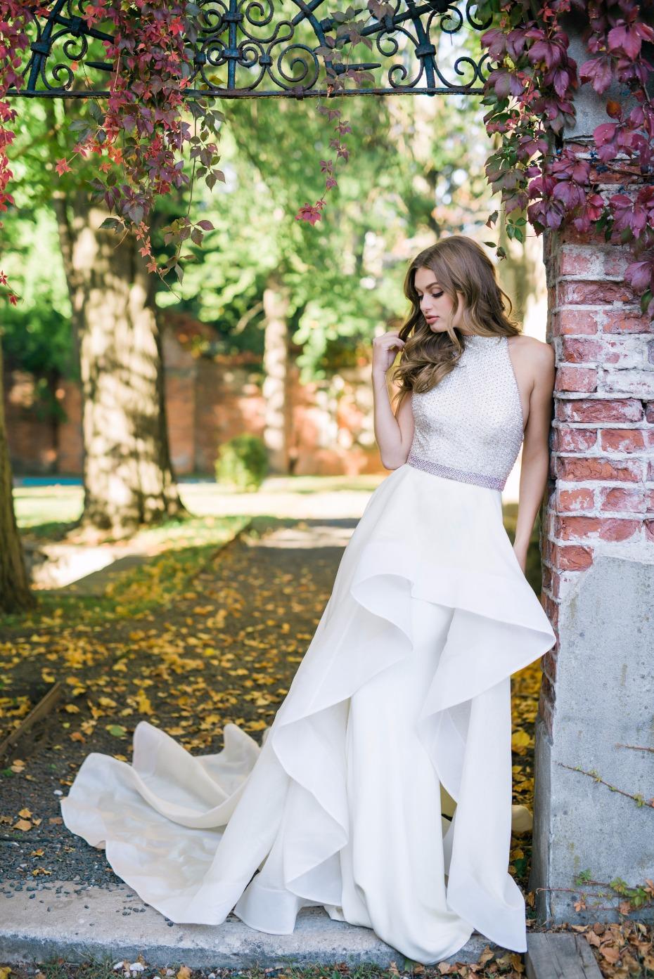 Beautiful floor length fit and flare off white bridal gown with high low skirt and train features embellished sleeveless bodice with high neckline.