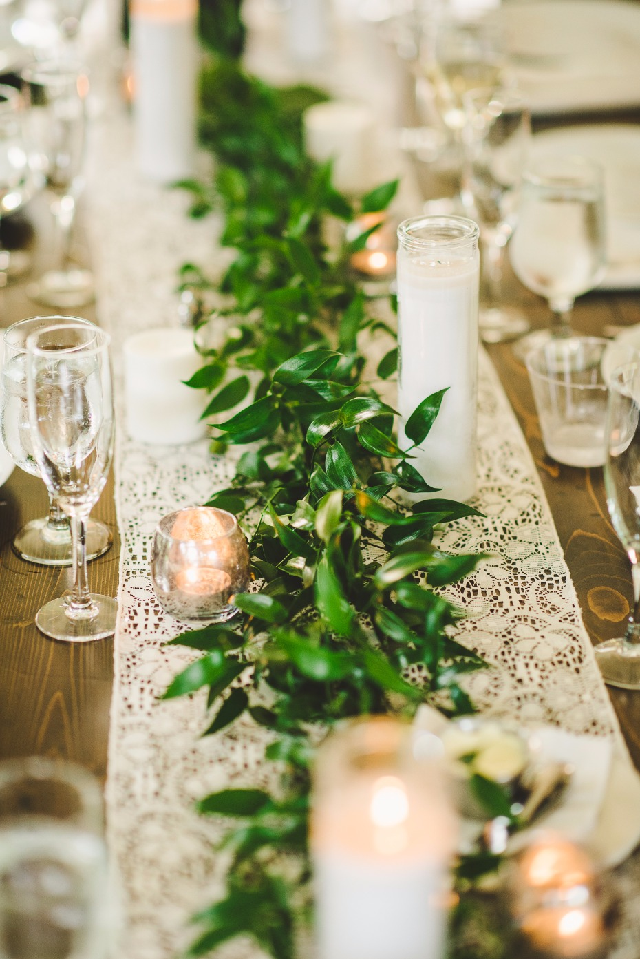 greenery garland on top of a lace table runner