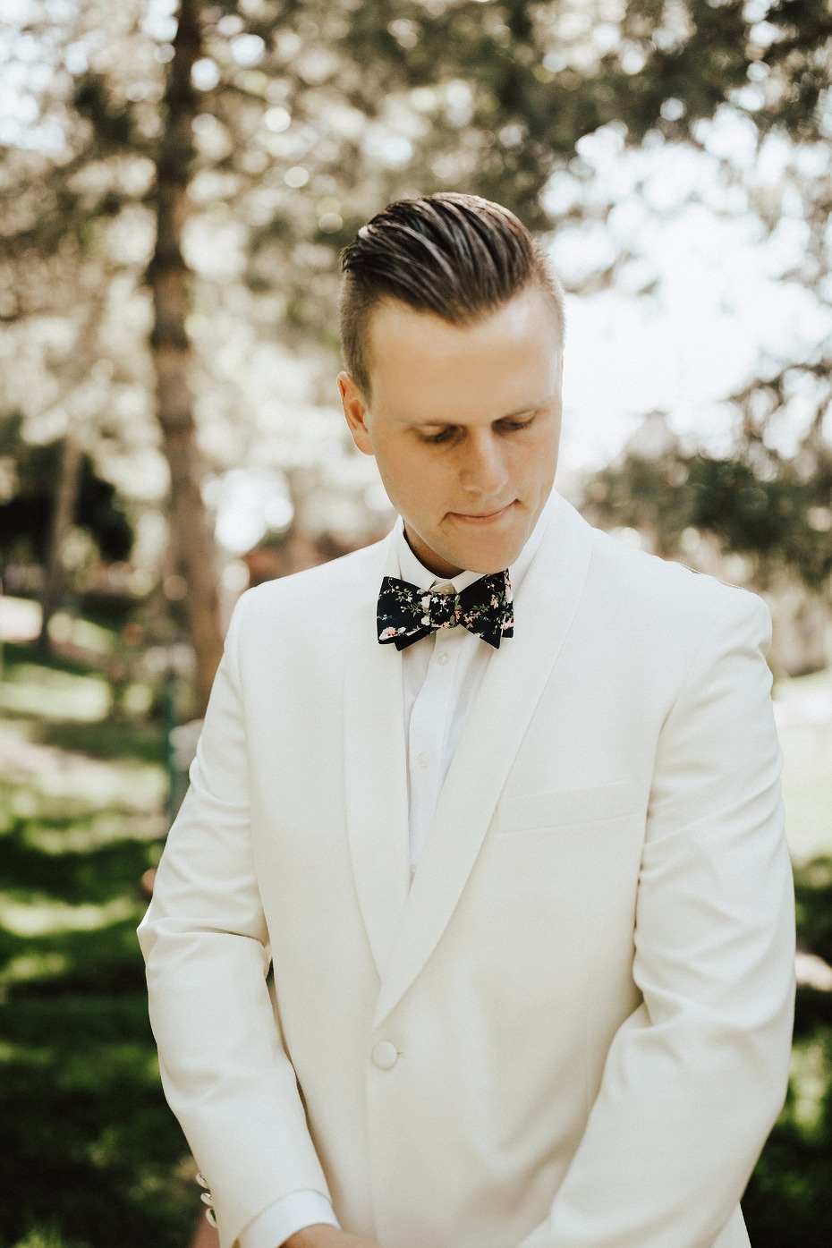 groom in white dinner jacket and bow tie