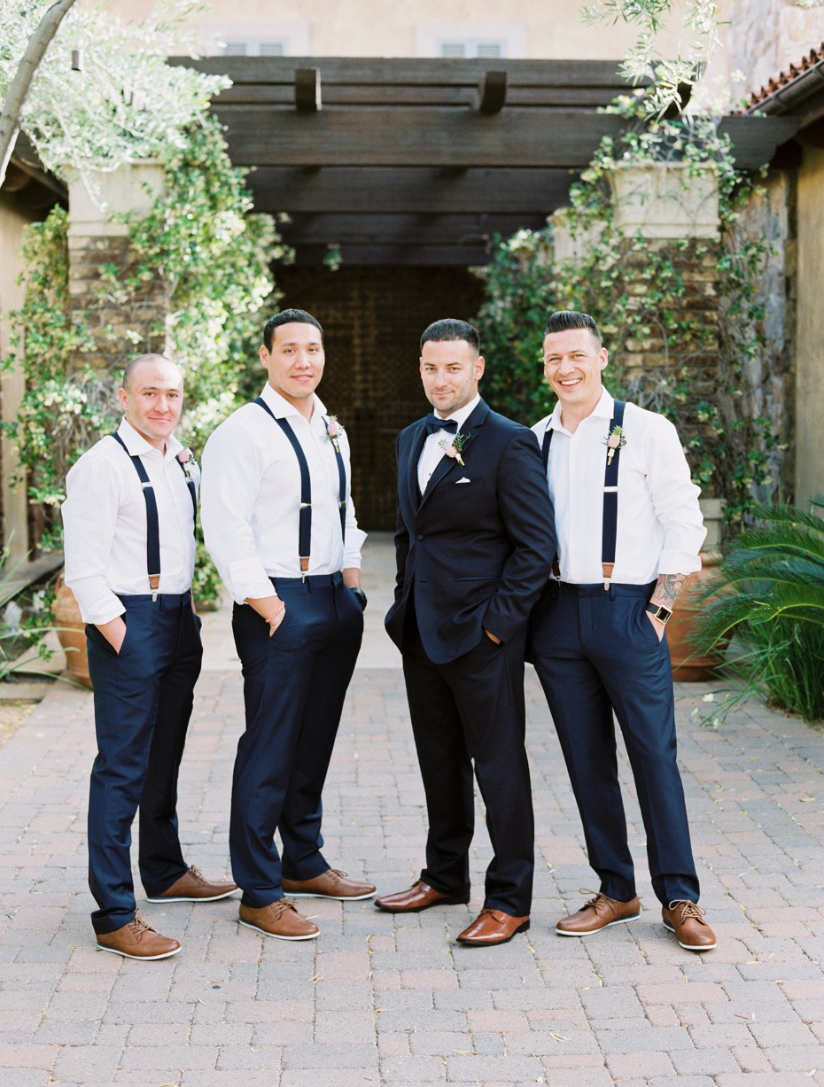 groom in navy suit and groomsmen in suspenders and navy slacks