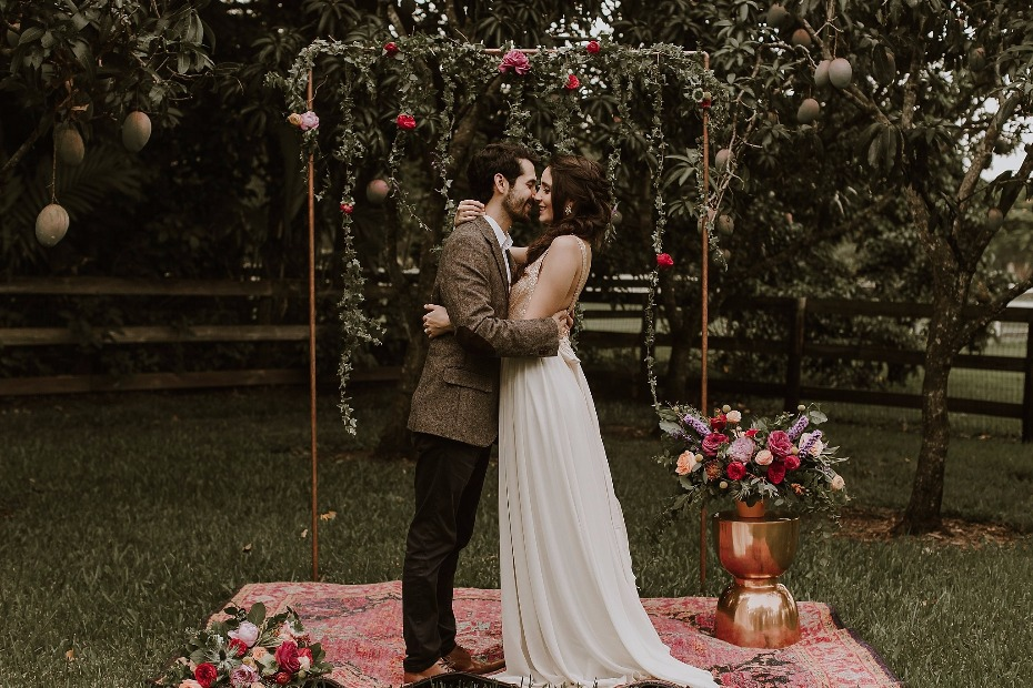 Colorful boho ceremony with rugs and gold
