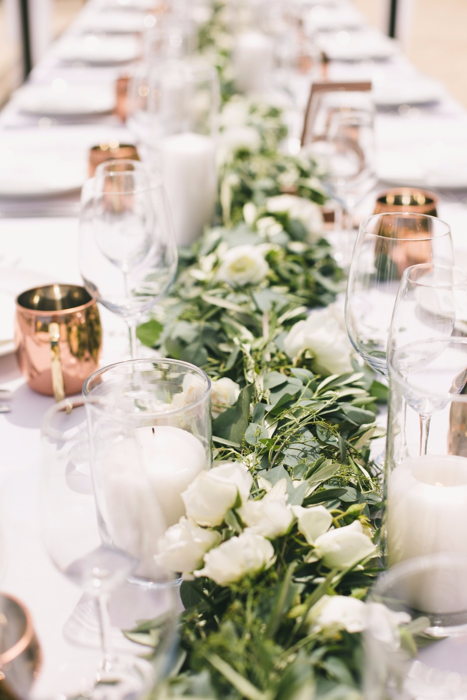 Greenery centerpiece with white candles and flowers