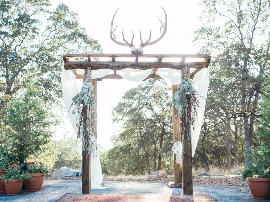 hand made wedding arch with antler rack and draped curtains