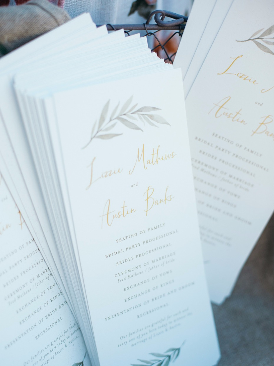 wedding programs with elegant greenery and gold calligraphy