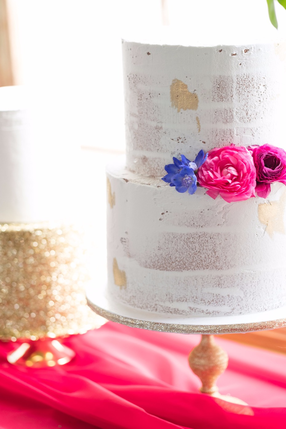 nearly naked wedding cake accented with jewel tone flowers