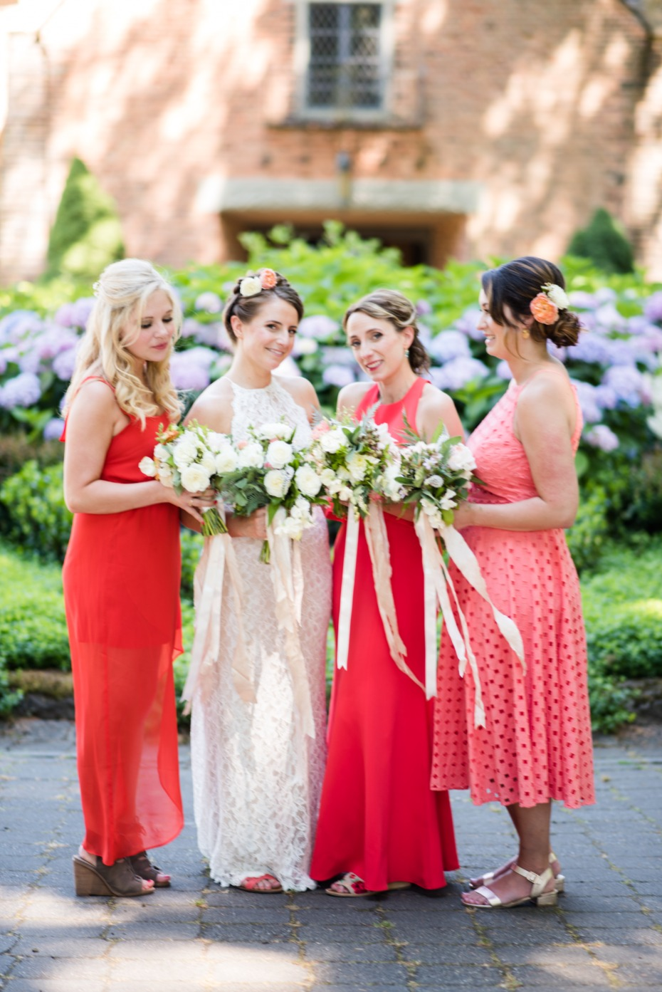bride and her bridesmaids in varying shades of coral