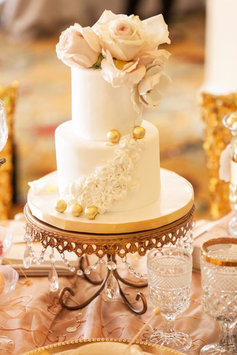 Ivory Tiered Wedding Cake with blush flowers on gold chandelier cake stand by Opulent Treasures