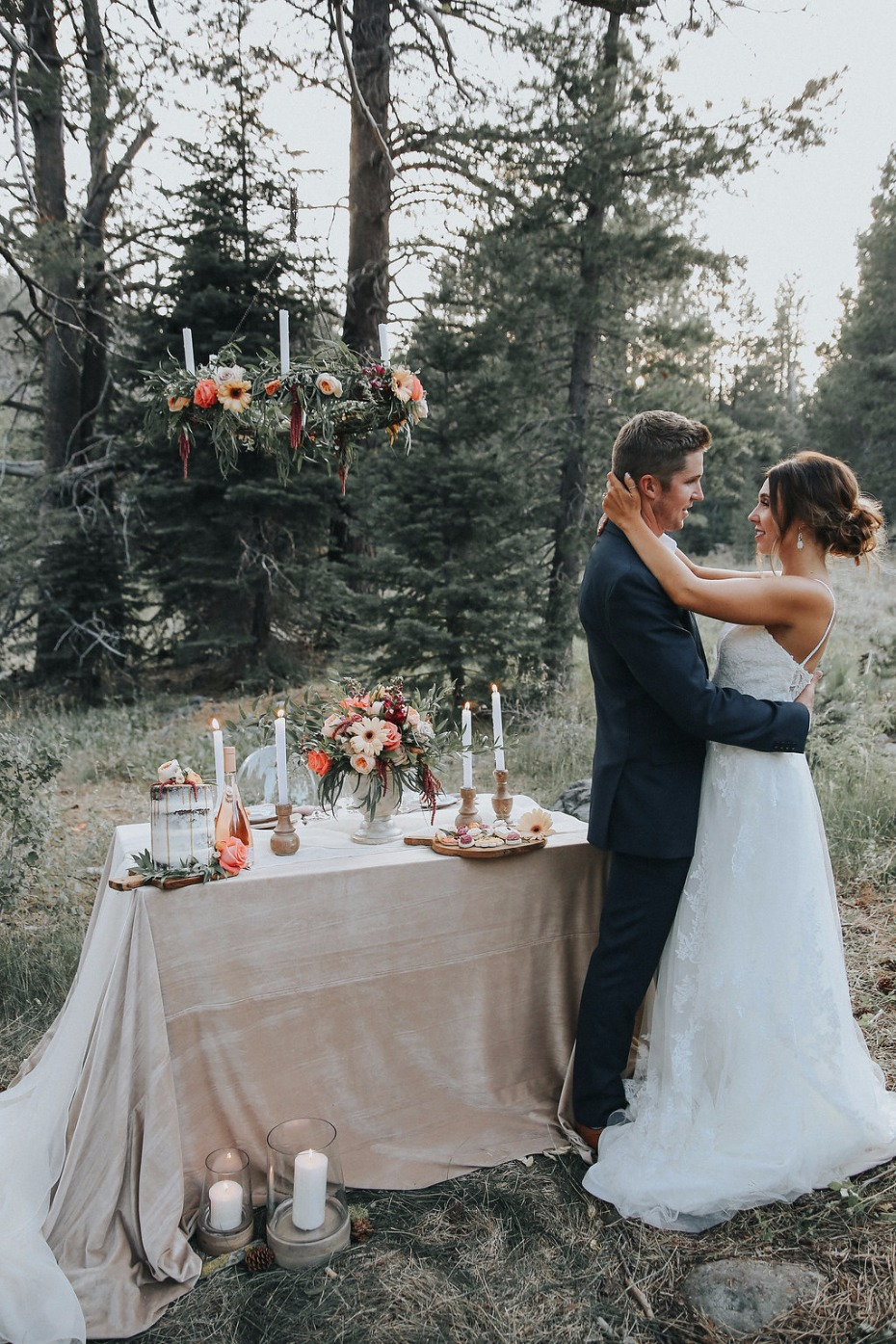 glamorous mountain sweetheart table with floral chandelier and plenty of candles