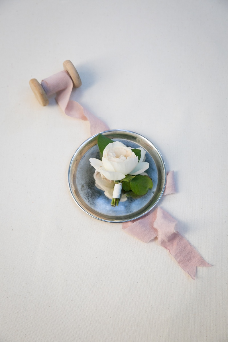 A simple garden rose for a boutonnière styled with raw silk ribbon on a silver tray Photo by Miki & Sonja Photography Styling
