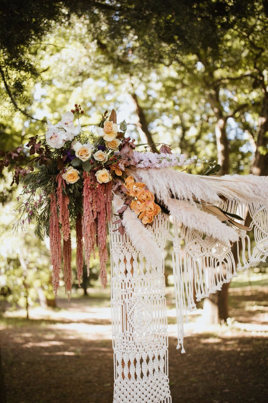 Macrame ceremony backdrop with florals